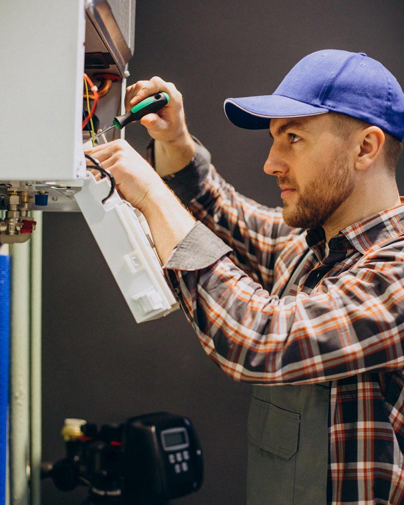 Service man adjusting house heating system